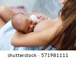 mother breastfeeding her... | Shutterstock . vector #571981111