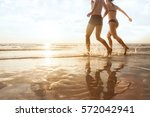 happy young couple running to...   Shutterstock . vector #572042941