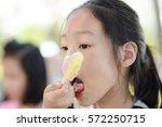 portrait of asian girl licking... | Shutterstock . vector #572250715