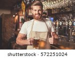 handsome bearded bartender in... | Shutterstock . vector #572251024