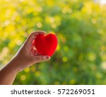 hand holding a red heart on... | Shutterstock . vector #572269051