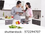 man smelling his wifes cooking | Shutterstock . vector #572294707