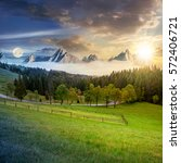 time concept of day and night change in composite summer mountain landscape. rural valley with fence on a  grassy meadow. curve road goes to the spruce forest in front of a huge ridge with rocky peaks - stock photo