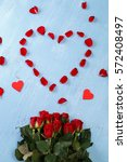 Stock photo heart of red rose petals on blue painted rustic background valentines day or love concept fresh 572408497