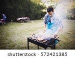 handsome man preparing barbecue ... | Shutterstock . vector #572421385