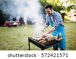 handsome man preparing barbecue ... | Shutterstock . vector #572421571