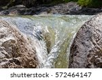 water flows through stones in a ... | Shutterstock . vector #572464147
