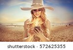 attractive blonde texing on... | Shutterstock . vector #572625355
