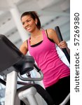 Beautiful gym woman exercising on a cardio machine smiling - stock photo