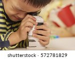 boy using microscope at home or ... | Shutterstock . vector #572781829