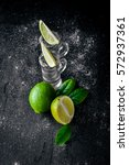 Small photo of Tequila with lime, lemon, and salt on a black background Wooden. Free space for text . Top view.
