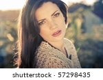 Young beautiful fashion model with hair and make-up professionally done outdoors backlit at sunset - stock photo