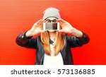 Small photo of Fashion cool girl taking picture on smartphone self portrait, screen view, over red background