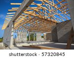 New home Construction of a cement block home with wooden roof trusses view from outside looking in. - stock photo