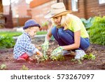 Child And His Mother Planting...