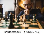 a young man playing chess... | Shutterstock . vector #573389719
