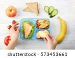 mother putting food in lunch... | Shutterstock . vector #573453661