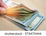 hand counting us dollar bills... | Shutterstock . vector #573475444