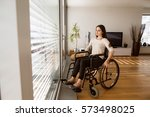 Small photo of Upset disabled woman in wheelchair at home in living room.