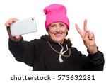 Small photo of Funny granny makes a selfie. A white smartphone in one hand and other hand shows a peace sign. Nonchalant pensioner shares her uplifted mood through a social media post.