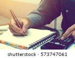 asian young man doing finances... | Shutterstock . vector #573747061