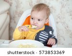 little baby boy eating sitting... | Shutterstock . vector #573853369