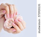 hands of a woman with pink... | Shutterstock . vector #573920131