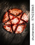 Small photo of Shadowed still life photo on a cursed pizza sliced into pieces of a Luciferian star. Opening hells gate
