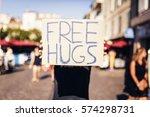 man holding free hugs sign in... | Shutterstock . vector #574298731