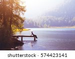 happy woman sitting on the pier ... | Shutterstock . vector #574423141