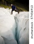 Man bridges the gap on a deep crevasse on a glacier, New Zealand - stock photo