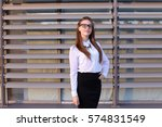 Small photo of Ambitious modern young women woman, business woman, student posing for camera, smiling, change posture, standing on background of large gray window of business center outdoors. Girl with blond hair