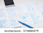 Small photo of Creating mobile responsive website, wireframe sketches and blue marker pen on designer desk