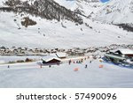 Ski scenario: Skiers approaching chairlift, mountains and village in the background - shot in Livigno, Italian Alps - stock photo