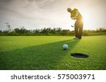 golfer putting golf ball on the ... | Shutterstock . vector #575003971