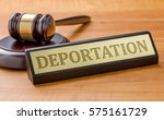Small photo of A gavel and a name plate with the engraving Deportation