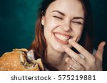 Small photo of Woman laughing and eating a hamburger, hamburger and smile.