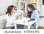 two female friends do a manicure | Shutterstock . vector #575441491