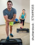 Small photo of Portrait of man and woman doing aerobic exercise with dumbbell on stepper