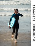 surfer woman leaving the sea... | Shutterstock . vector #575499961