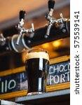 Small photo of Nonic pint glass with dark stout ale standing on a pub counter near draft taps