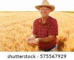 senior farmer in field holding...