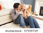 Stock photo couple taking playing with pet cat at home 57559729