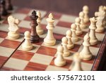 black king surrounded by white... | Shutterstock . vector #575672101