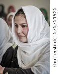 Small photo of Afghanistan - circa October 2011: Young pretty girl wears white hijab and smiles nicely at ADRA school in Afghanistan. Documentary editorial.