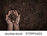 man  farmer's  hands on soil...