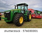 Small photo of KAMEN, CZECH REPUBLIC - September 10, 2013: John Deere tractor with attached Pottinger seeder, cloudy sky on background