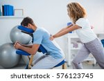 physiotherapist giving back... | Shutterstock . vector #576123745
