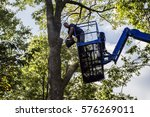 man on aerial platform cutting... | Shutterstock . vector #576269011