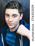 Small photo of A young man shows the fist problem. The transition to adulthood, on the face pimples